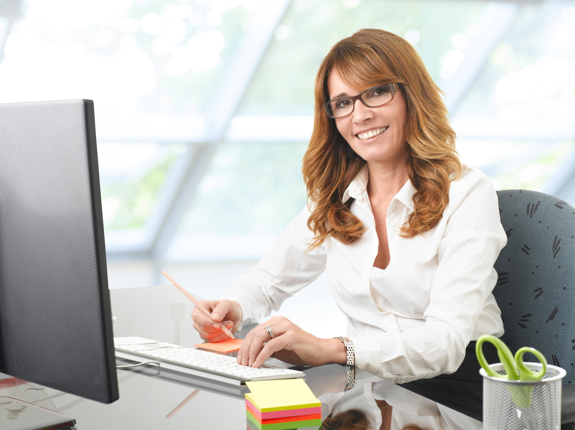 Smiling businesswoman at office desk with a computer